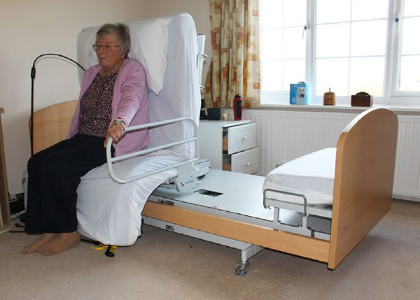 Woman holding handrail on rotating adjustable bed